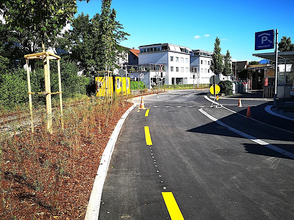 Die nach hinten erweiterte Migros in Cham im Neudorfcenter führt auch zu Veränderungen auf der Neudorfstrasse: Die oberiridischen Längsparkplätze sind nicht mehr da. Links daneben ist das Papieri-Bähnli-Gleis zu sehen, das zu einer Velo- und Fussgängerachse umgebaut wird.