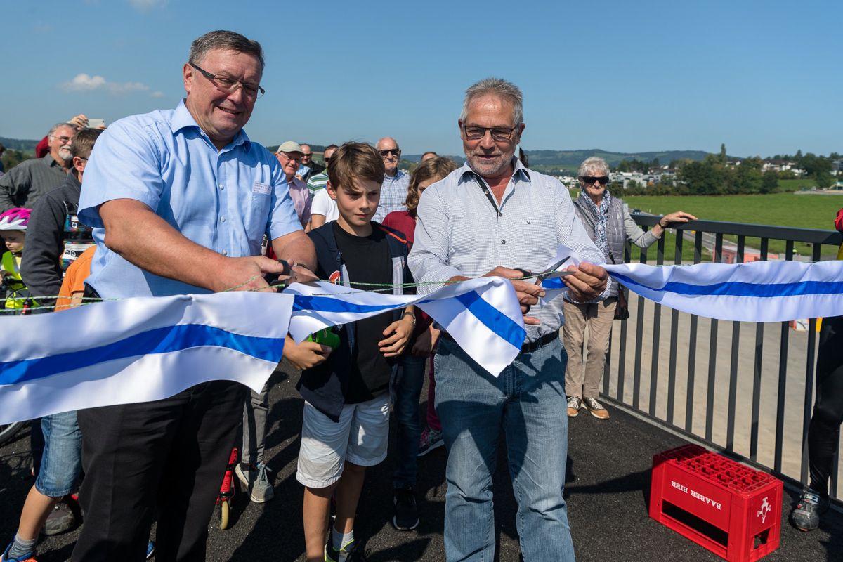 Der kantonale Baudirektor Urs Hürlimann (links) und der Baarer Bauchef Paul Langenegger durchschneiden das Band bei der Eröffnung der neuen Velobrücke über die Tangente.