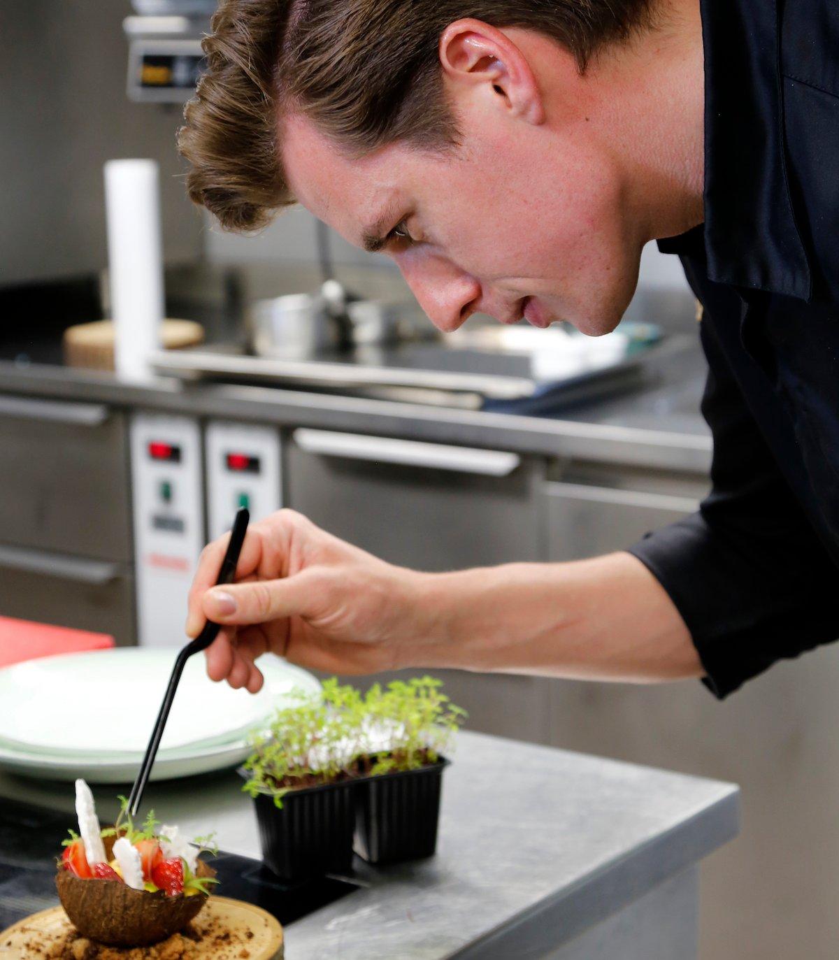 Leidenschaft und Präzision: Küchenchef Achtien gibt Kresse zur Dekoration bei.