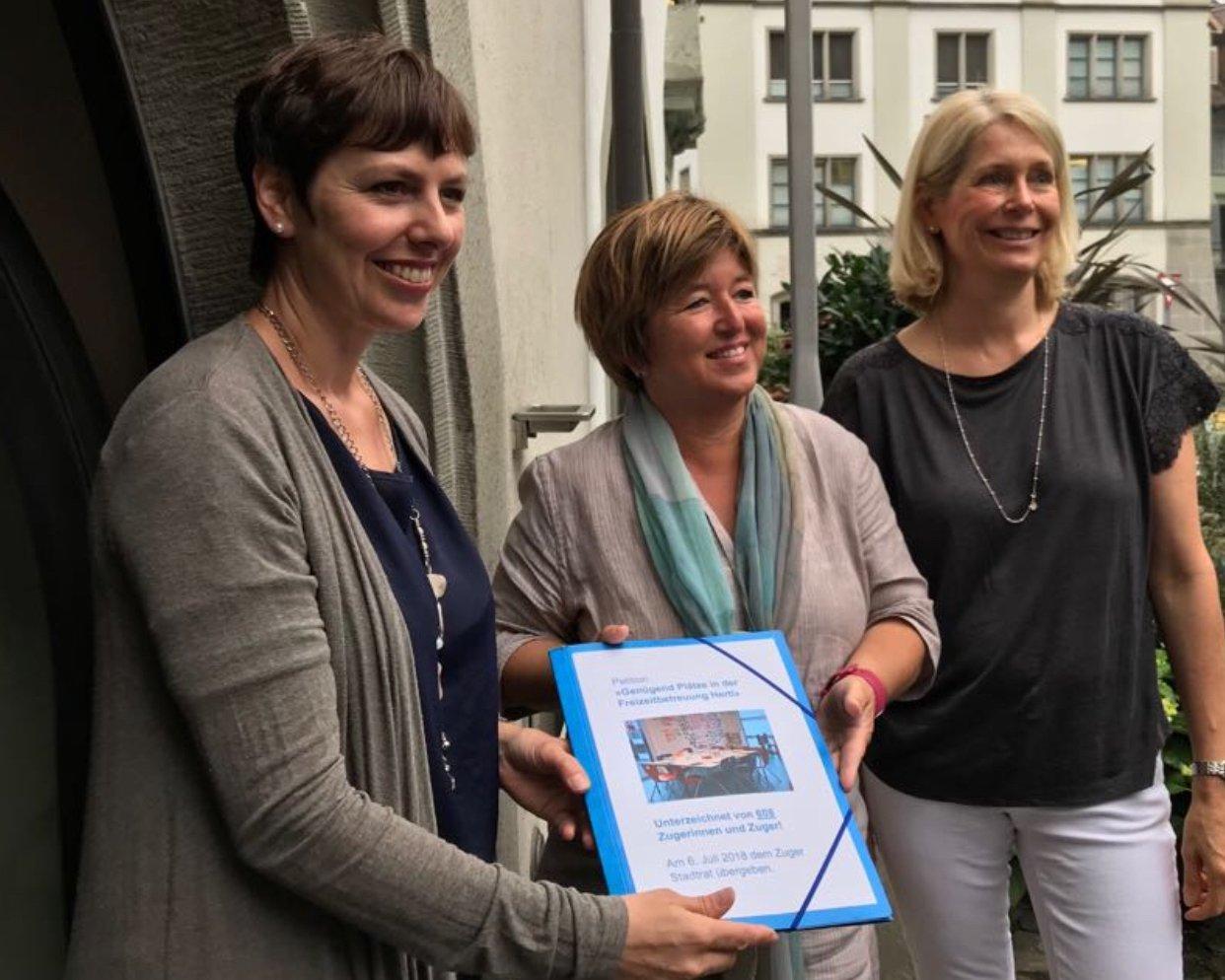 Alexandra Beeler (links) und Eliane Birchmeier (rechts) überreichen die Petition an Stadträtin Vroni Straub, Vorsteherin Bildungsdepartement.