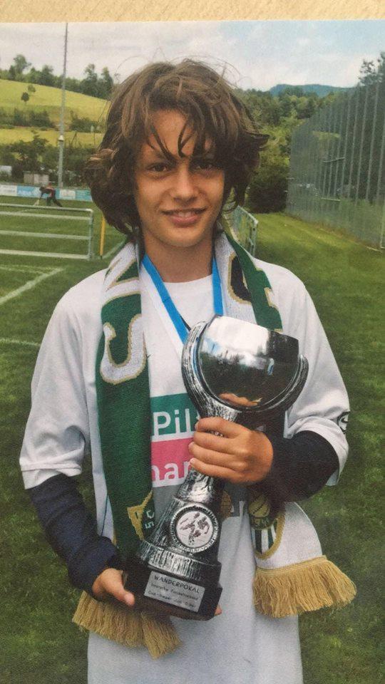 Stolz präsentiert der junge Olivier Kleiner den Pokal der D-Junioren.
