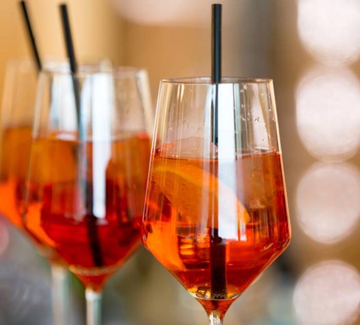 Leuchtet immer noch überall fröhlich in Orange: Aperol Spritz geht seit 1919 über die Tresen.