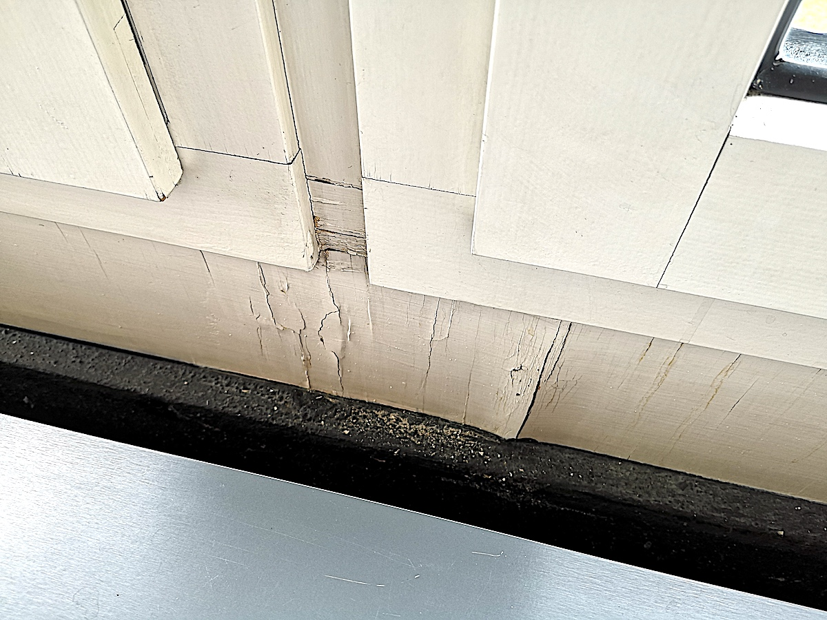 Schaden am Fenstersockel durch eindringende Feuchtigkeit: Die Holzverkleidung ist aufgequollen und zeigt Risse.