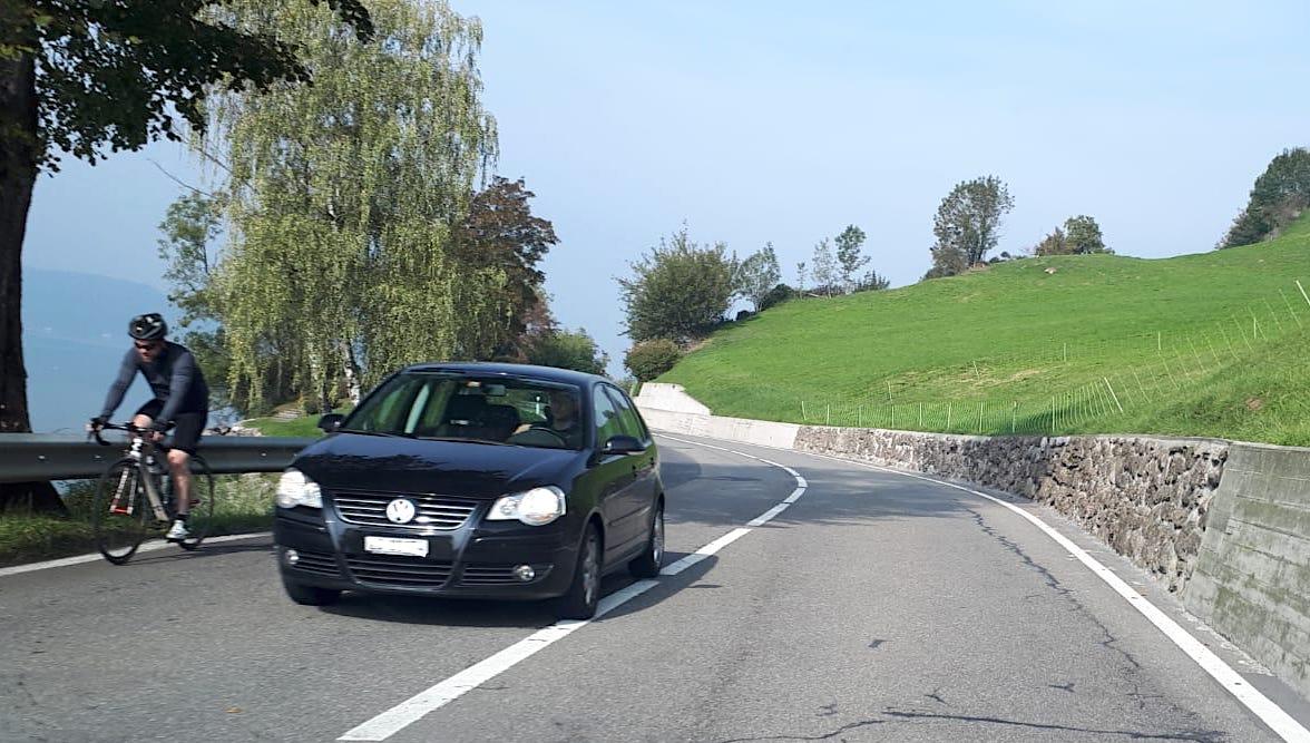 Keine Radstreifen, kein Trottoir: Velofahrer und Auto in der Nähe von St.Adrian.