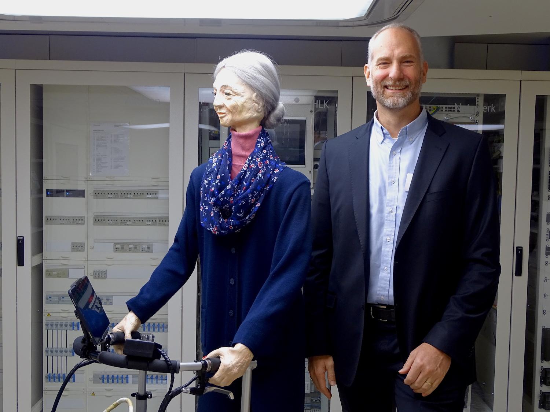 Andrew Paice, Leiter des iHomeLabs mit der Puppe «Anna». An ihr kann veranschaulicht werden, wo die Vorteile eines Smart Homes sind