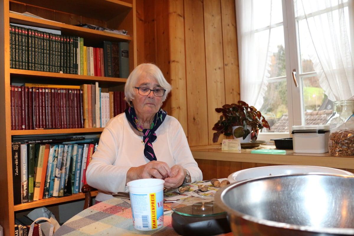 Berta Horat sitzt in ihrer Wohnung und knackt Baumnüsse.