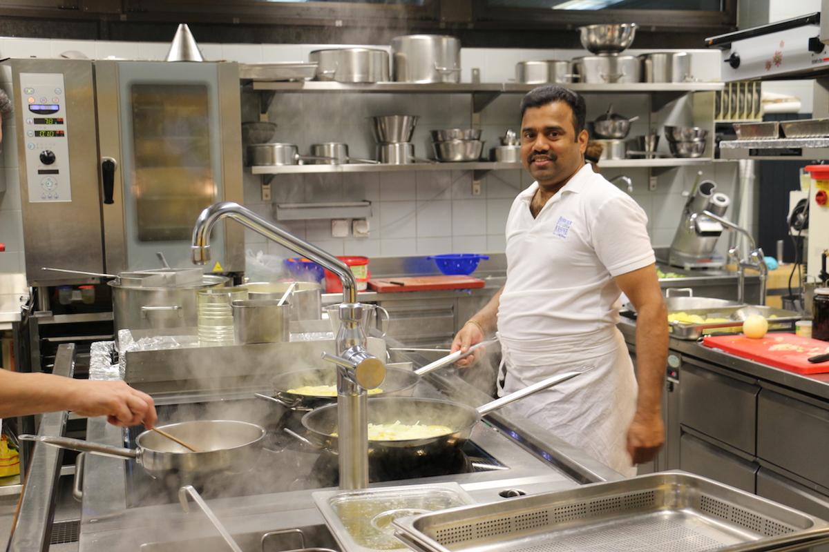 Lingam Yathurai steht in der Küche und bereitet das Mittagessen vor.
