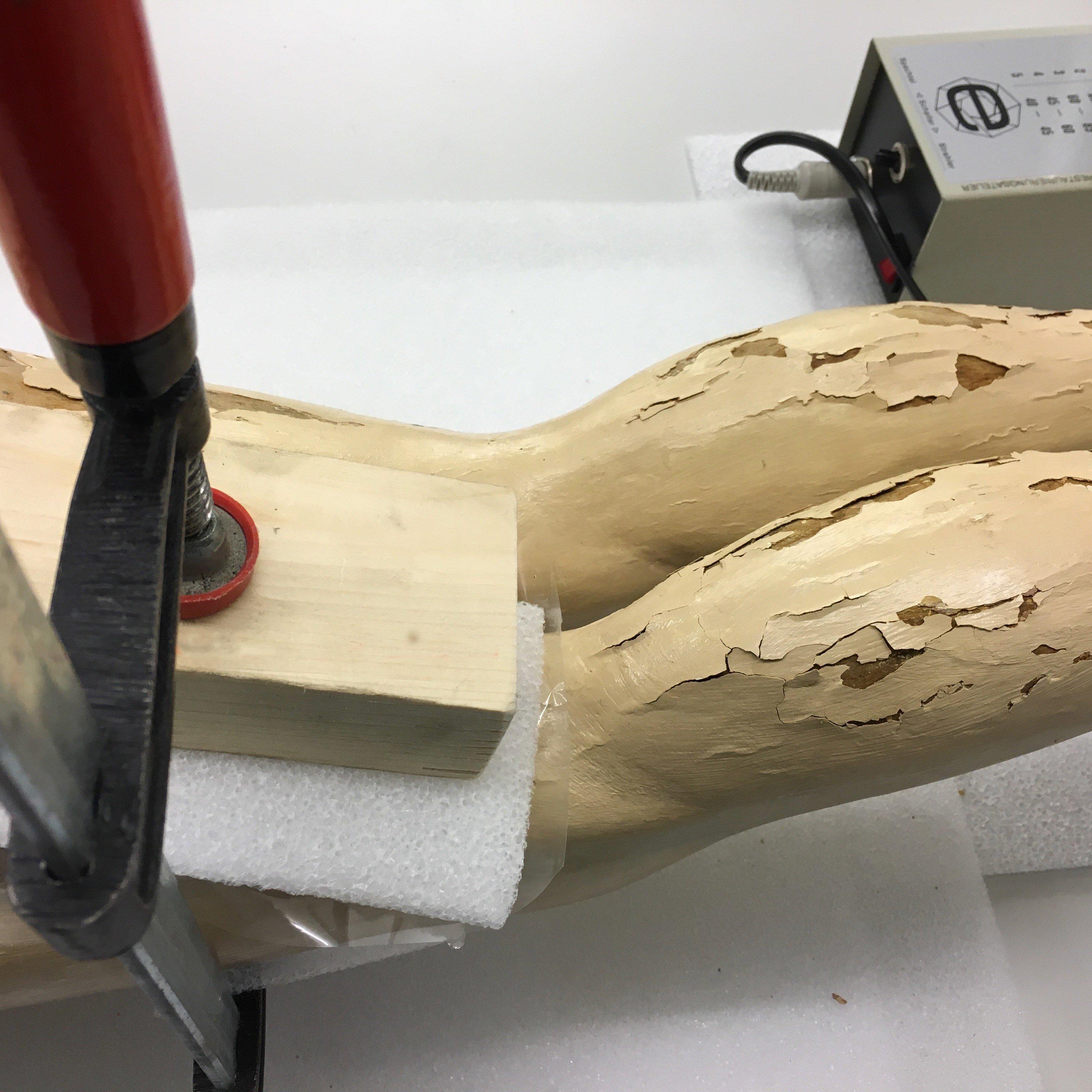 Mit Hilfe von Schraubzwingen und Holzstücken wird ein formbarer Schaumstoff auf die Farbschollen gepresst bis der Leim trocken ist. / Bild: Museum Burg Zug