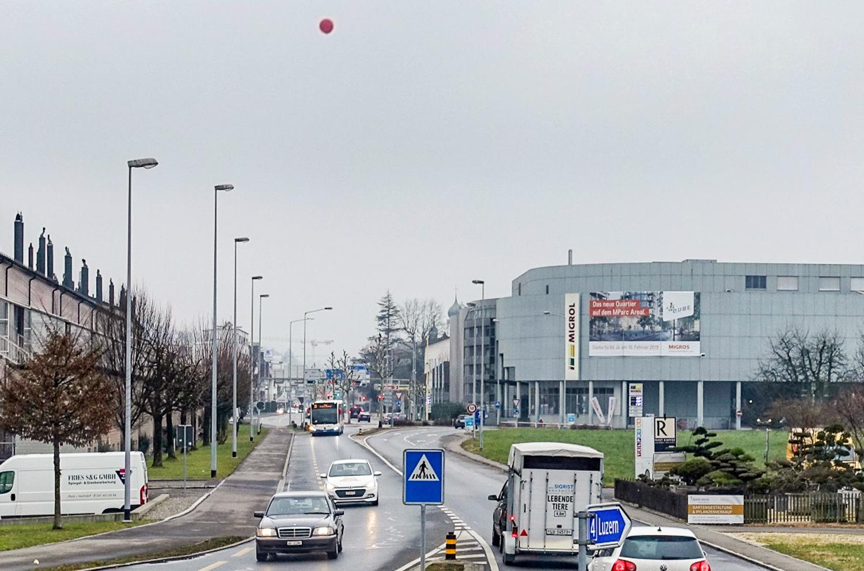 Mit einem roten Ballon – der windbedingt etwas stark in die Strassenmitte ragt – verdeutlichen die Gegner des Projekts die maximal zulässige Höhe des Wohnturms.
