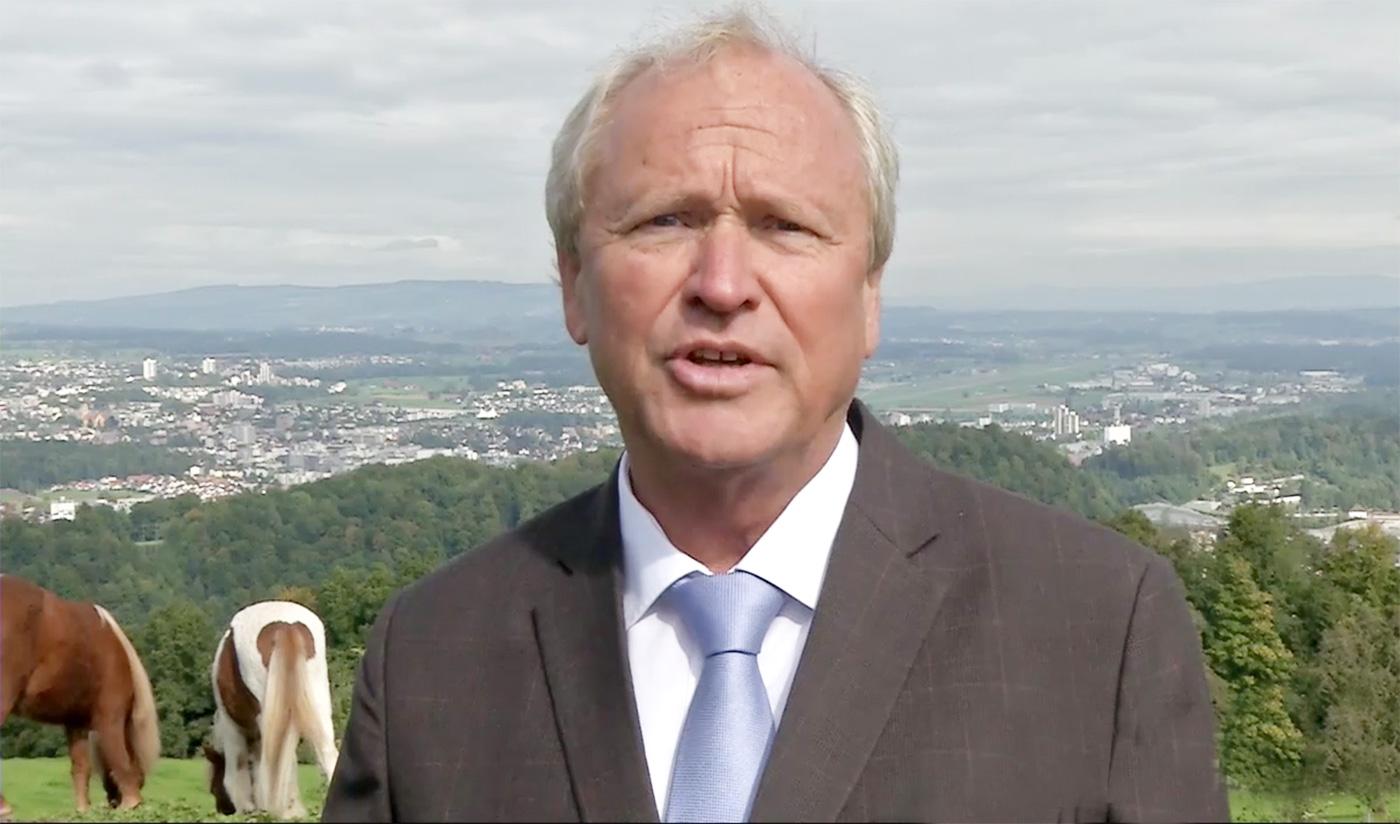 Paul Winiker hält seine Rede auf dem Sonnenberg vor grasenden Ponys.
