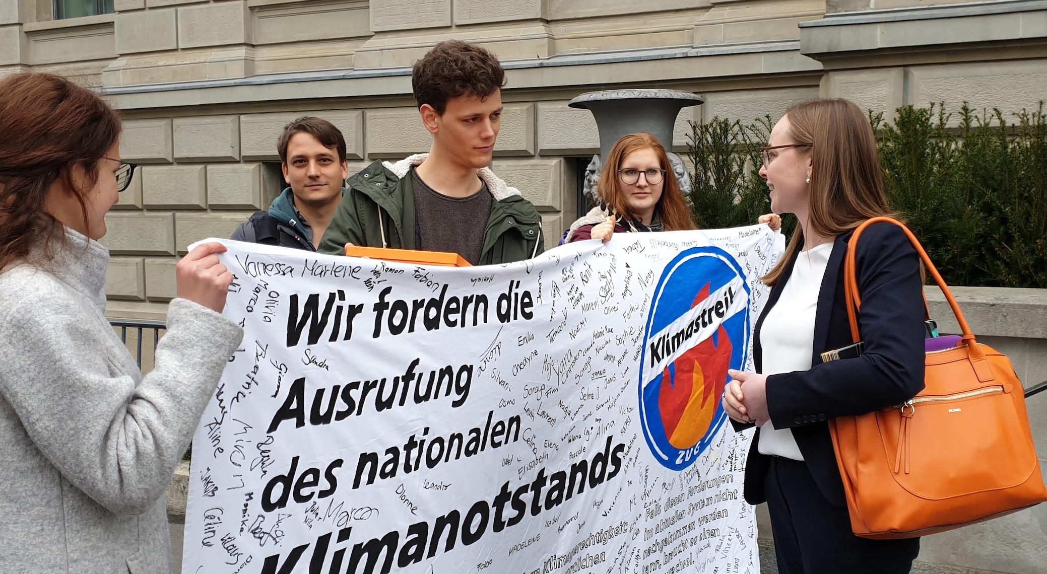 CVP-Präsidentin Laura Dittli (rechts) lädt die «Zuger Klima-Jugend» in Form von Tim Kilchsperger (Mitte) an den runden Tisch ein.
