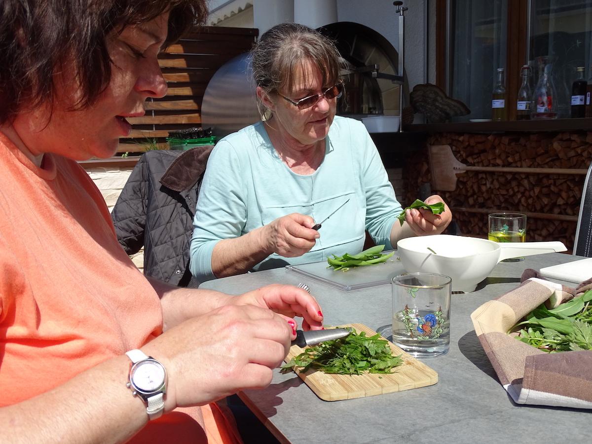 Die Teilnehmerinnen schnippeln die Kräuter für die Suppe.