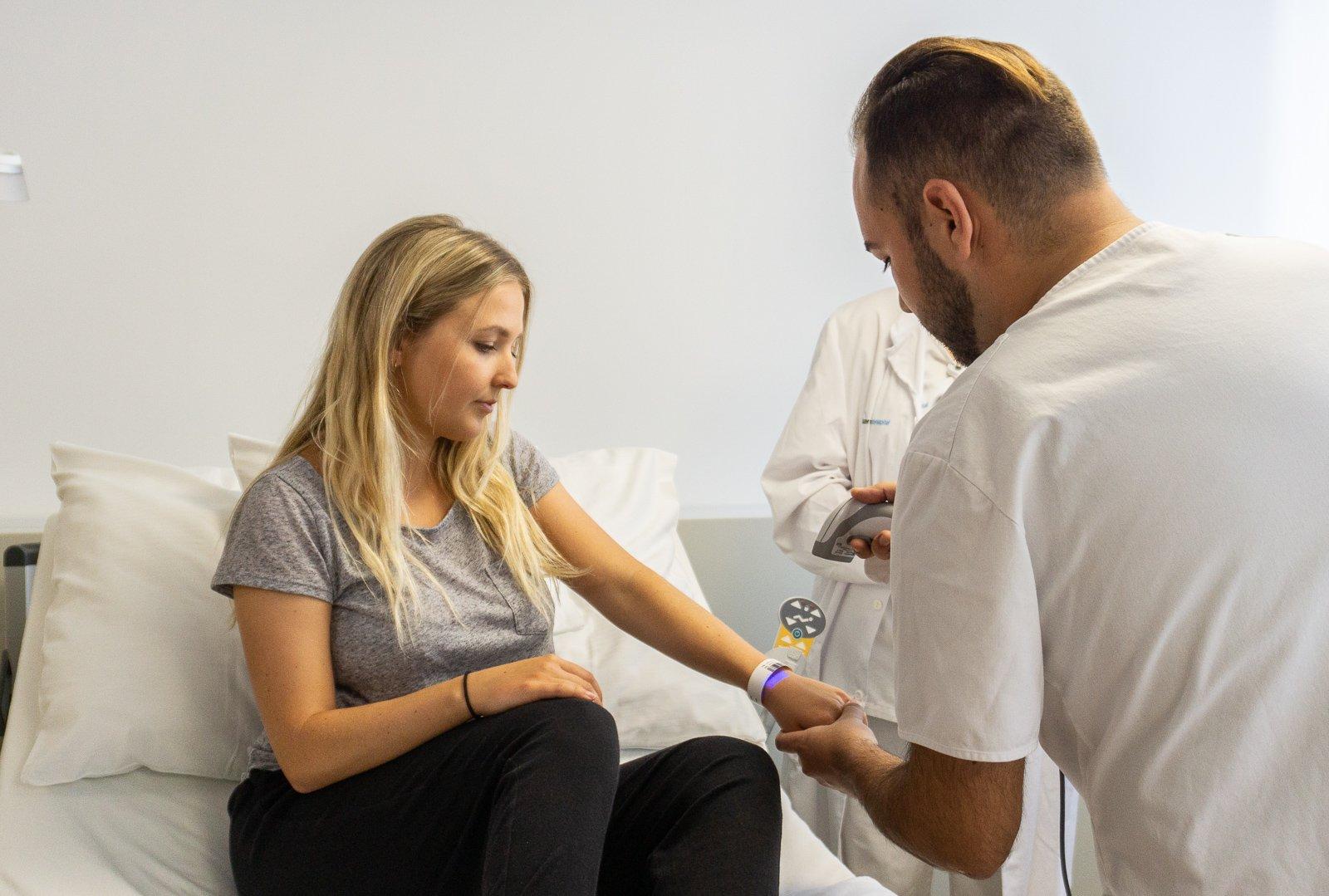 Der Pfleger kann mit einem Scanner die Daten der Patientin abrufen.